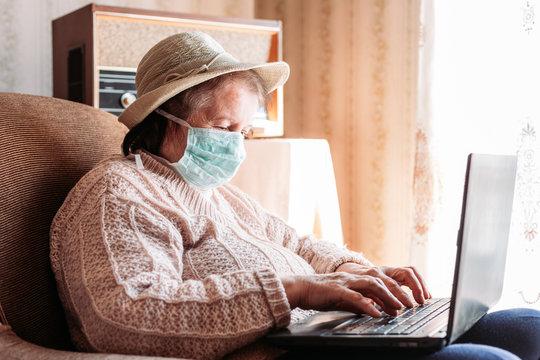 Elderly woman wearing a medical mask using her laptop, typing something.