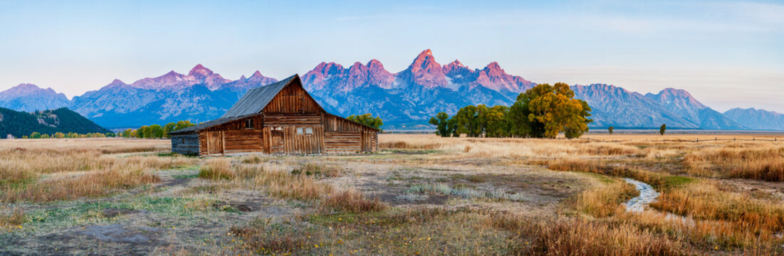 Panorama of the historic mormon barn in front of the Grand Tetons at sunrise, Grand Teton National Park, Wyoming