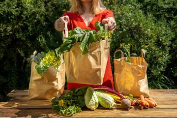 Une jeune fille tend un des trois sacs remplis de légumes du jardin  Fototapete