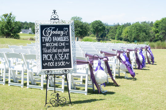 """Chalk board Wedding ceremony sign in white frame that reads """" Today two families become one. we ask that you pick a seat not a side"""" at ceremony isle"""