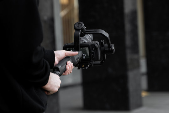 Professional videographer in black hoodie holding professional camera on 3-axis gimbal stabilizer. Filmmaker making a great video with a professional cinema camera. Cinematographer.