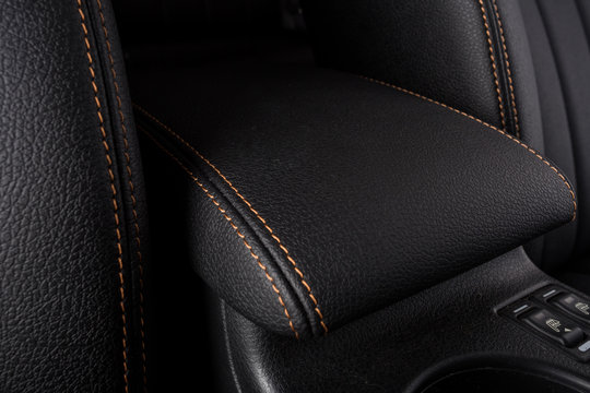the interior of the car is covered with handmade genuine leather. Car leather black armrest. front view. High-quality stitching with gold threads and skin texture are visible