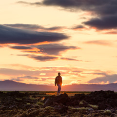 Wall Murals Cappuccino silhouette of a man on a rock at sunset, iceland