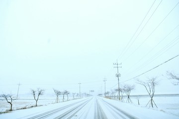Foto auf AluDibond Licht blau Road On Snow Covered Landscape Against Clear Sky