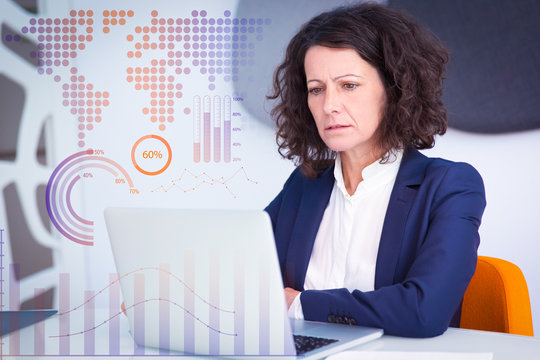 Woman getting concerning news and virtual statistic graphics. Business woman sitting at white conference table, using laptop, staring at screen and reading. Bad news concept