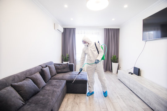 Disinfector in a protective suit conducts disinfection in contaminated area of house to prevent coronavirus. Health car.