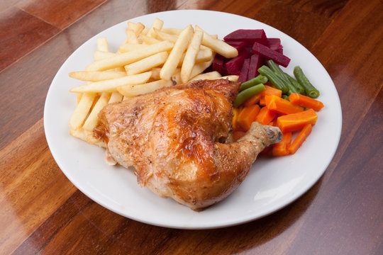 Peruvian food: pollo a la brasa or roasted chicken with french fries and cooked vegetable salad served on a white plate