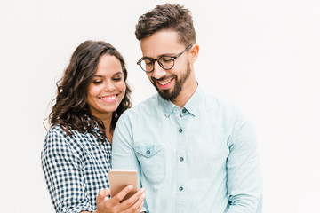 Obraz Happy cheerful woman showing message on phone to her boyfriend. Young woman in casual and man in glasses in glasses posing isolated over white background. Good news concept - fototapety do salonu