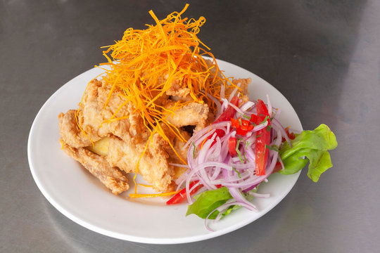 Peruvian food: chicharron de pescado or fish cracklings with fried cassava and onion salad with chili, served on a white plate