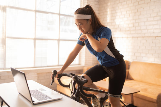 Asian woman cyclist. She is exercising in home. by cycling on the trainer.she is wiping sweat