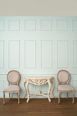 Vintage seat and classical carved wooden table on green background,elegant room with a patterned...