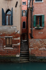 VENICE, ITALY February 16 , 2020.Picturesque Venice's red buildings with green windows near at canal