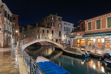 VENICE, ITALY - February 19, 2020: Night view of the romantic Venice with restaurants , bridges and canals