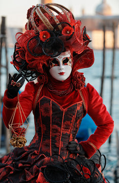 Venice Italy, February 18 2020. Woman with red costume posing for the camera at St Mark's Square during Venice Carnival (Carnivale di Venezia