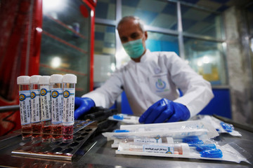 An Iraqi doctor sticks labels on locally made testing components for the coronavirus disease (COVID-19), as it's produced by a group of researchers from Basra University, in Basra
