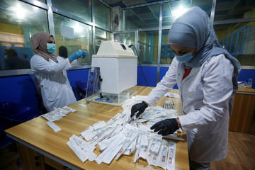 Iraqi doctors stick labels on locally made testing components for the coronavirus disease (COVID-19), as it's produced by a group of researchers from Basra University, in Basra