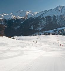 Fototapete - View down a piste in alpine ski resort