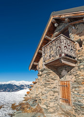 Wall Mural - Panoramic view across snow covered slope on alpine mountain with small house