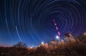 Night sky star trail over the television mobile radio tower