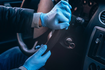 A man holds the steering wheel of a car in protective medical gloves. Hands close-up. Safe drive in a taxi during pandemic coronavirus. Protect driver and passengers from bacteria and virus infection
