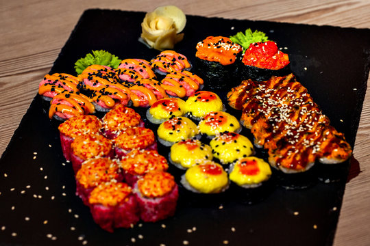 Hot baked set of rolls on a black plate with wasabi and ginger