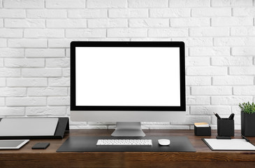 Modern computer with blank screen on table near brick wall. Space for design