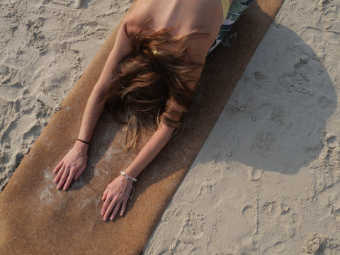 Top view of woman practicing child's yoga pose lying at cork mat at sandy beach