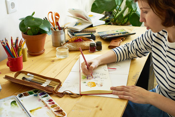 Close-up image of artist drawing in a sketchbook. Female designer working from home. Creative cozy workplace