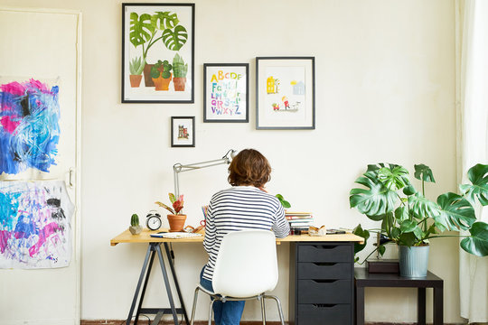 Female artist at her workplace working from home during self-isolation. Young woman dressed in jeans and striped shirt sitting at the table turned backwards. Creating an illustration.