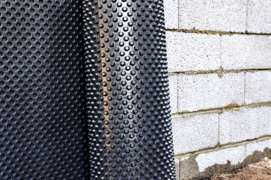 basement wall waterproofing - installing dimple geomembrane