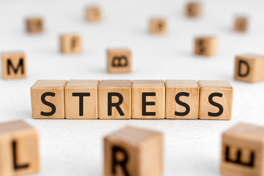 Stress - word from wooden blocks with letters, great worry caused by a difficult situation stress concept, random letters around white background