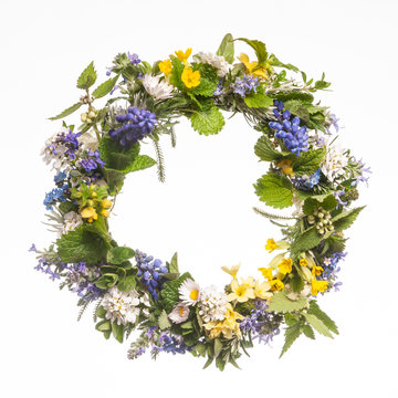Wreath of wild spring flowers on white background