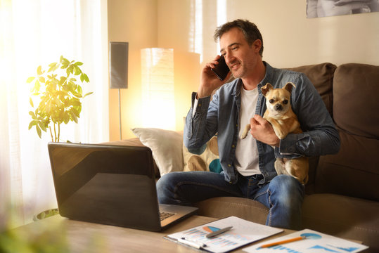 Man working from home talking on phone with his dog