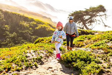 A young girl and her mother hiking together on a sunny day near the Pacific Ocean with warm clothes. Fotomurales