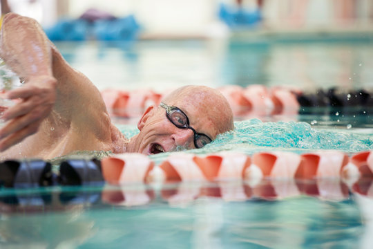 Close up shot of man in his mid 70s swimming laps in a pool.
