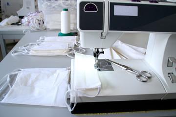Herz aus Garn auf der Nähmaschine. Herstellung von Mundschutzmasken aus Baumwollstoff in einer Manufaktur um die Gesundheit vor einer Infektion mit dem Coronavirus zu schützen
