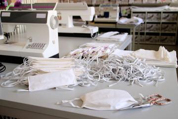Schneiderei mit Nähmaschinen, Baumwollstoff und Gummilitze bei der Produktion von Gesichtsmasken als Schutz gegen Corona Virus Pandämie in der Welt