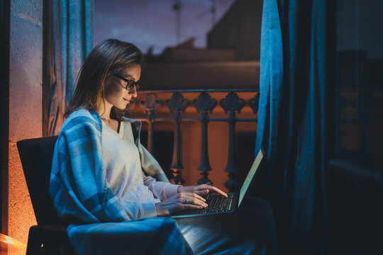 Home Office Late At Night, Young female professional copywritter in chair working at home, businesswoman working at night in homewear and eyeglasses using laptop computer reading email from client