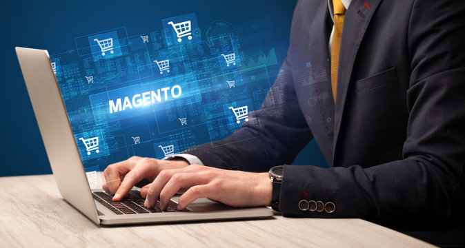 Businessman working on laptop with MAGENTO inscription, online shopping concept