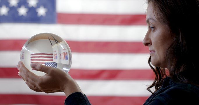 CU profile young Caucasian woman holding up crystal ball showing voting booths in front of US flag