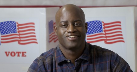 """Close up African American man in plaid shirt, posing and smiling in front of polling booths with US flag and """"Vote"""" printed on them. Large US flag behind, on back wall."""