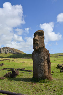 singular Ancient maoi statue in landscape with mountain and feilds