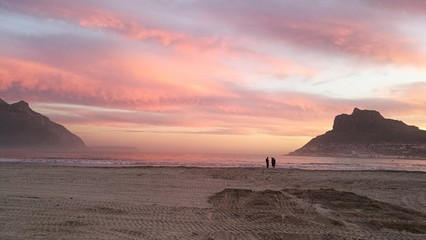 Distant View Of Men Standing At Beach Against Sky During Sunset