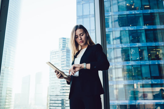 Confident caucasian female manager checking notification on wearable smartwatch with touchscreen and apps standing in office, millennial business woman in elegant formal wear using modern gadgets