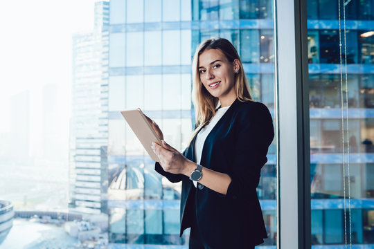 Half length portrait of cheerful female intelligent manager looking at camera using digital tablet for research in office, smiling business woman in elegant wear banking on touchpad enjoying gadget