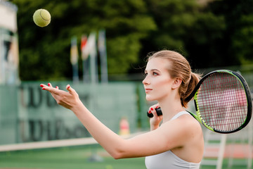 junior tennis player tossing ball up before pitching on court with racket