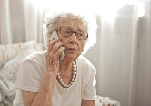 Elderly woman sitting on a call with a worried look on her face
