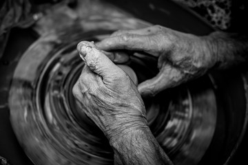 Hands of the potter. The potter makes pottery dishes on potter's wheel. The sculptor in workshop makes clay product closeup Wall mural