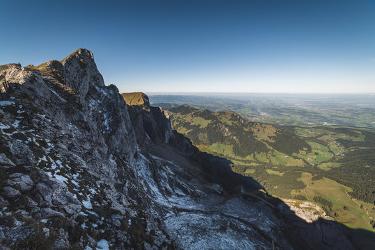 agged rock formations on Mount Pilatus overlooking a valley in the Swiss Alps with snowy mountain peaks in the background in Lucerne, Switzerland