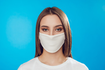 Woman wearing face protective mask on face against Coronavirus on the blue background.